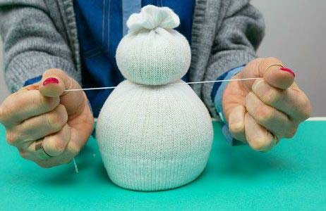 Теперь формируем снеговика, перевязав тело ниткой чуть выше середины