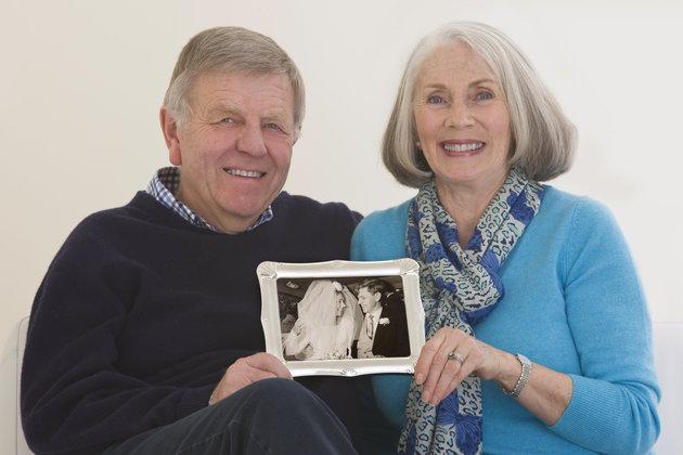 senior couple holding a framed wedding photogh