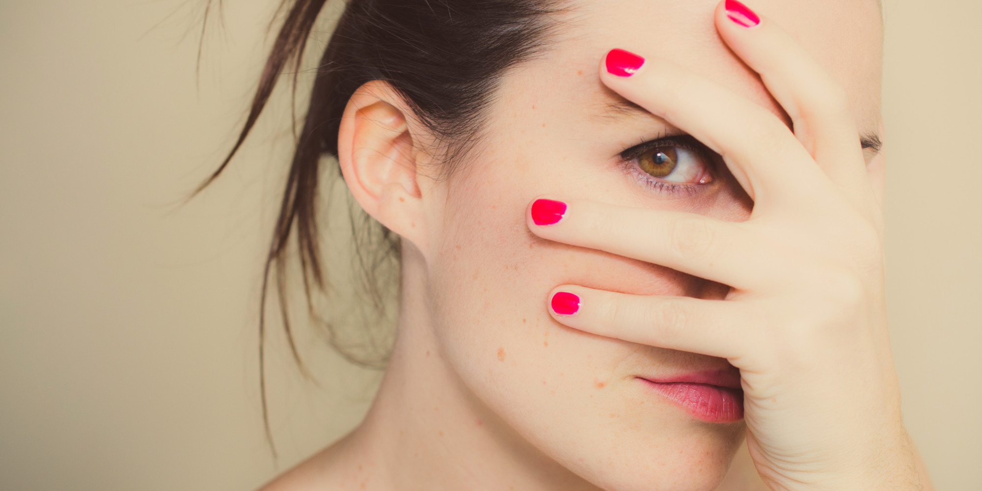 Misterious girl with red nails and hand on face.