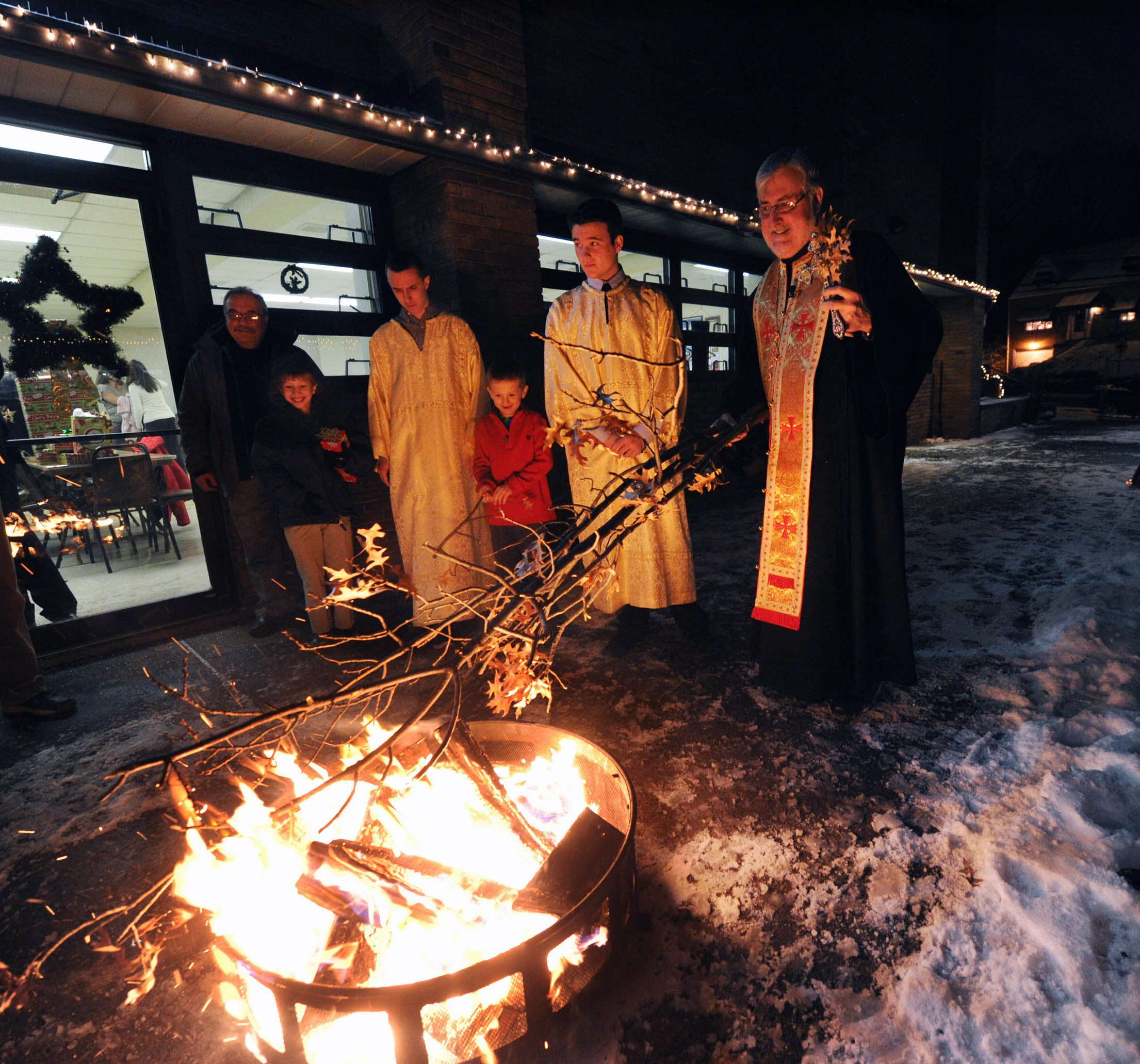 "John Heller / Post - Gazette Local / Yule Log McKeesport - Jan. 06, 2014 - Father Stevan Rocknage , right, Pastor of St. Sava Serbian Orthodox Church in McKeesport, oversees the burning of the ""Badnjak"" or Yule log .The ceremony is usually held out doors but due to extreme cold weather, the Orthodox Christmas Eve service was held in the parish hall under the church. Only the burning of the log was outdoors."