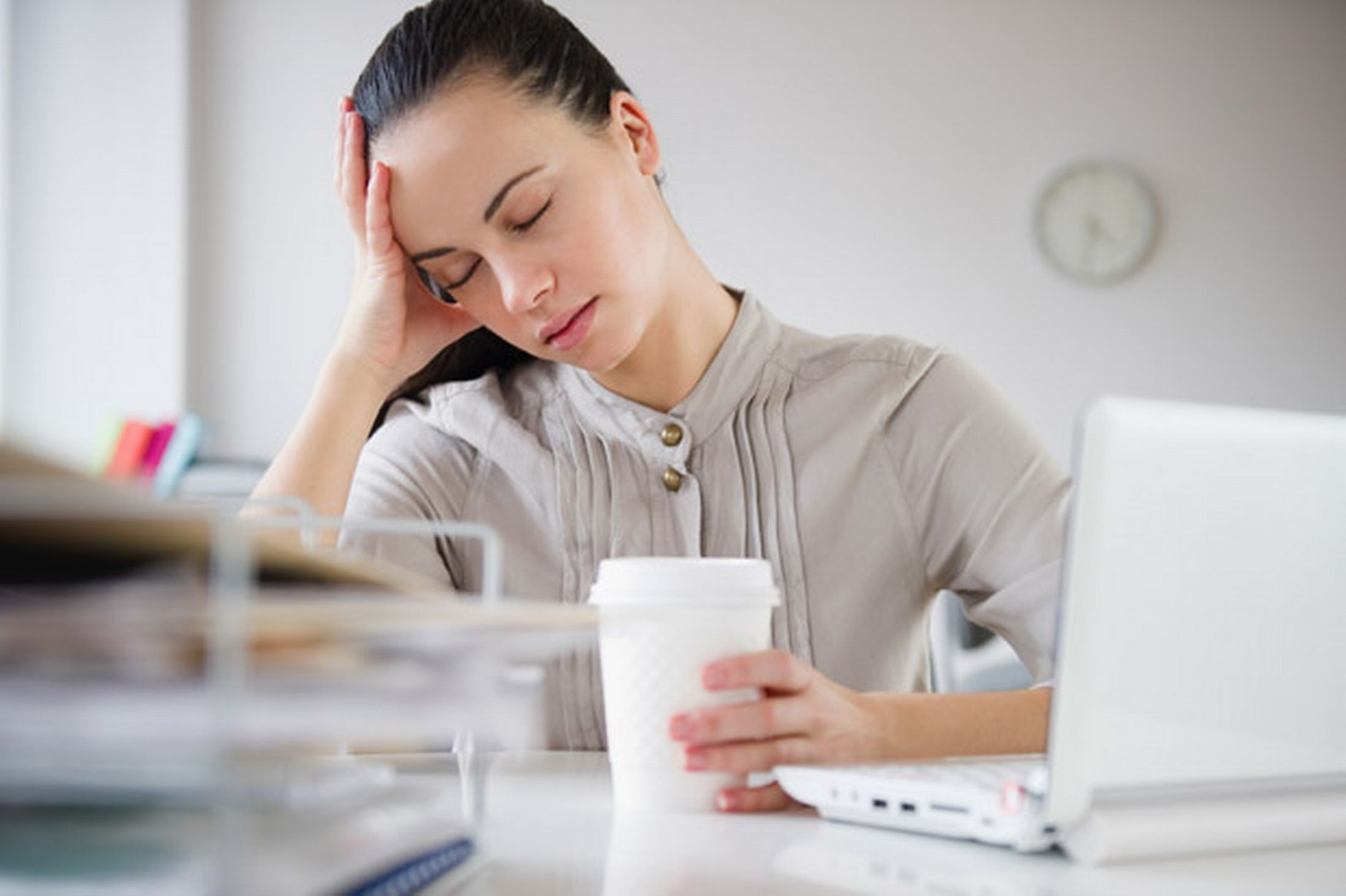 a-woman-exhausted-sitting-at-her-desk-with-a-cup-of-coffee